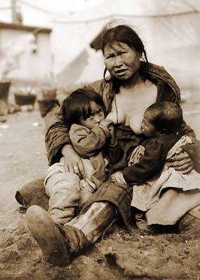 Inuit Eskimo woman breast-feeding two babies